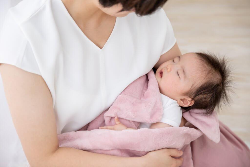 寝ている赤ちゃんをだっこする女性